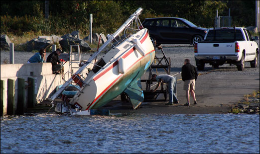 Assessing a sailboat mishap Monday evening at the boat slip next to the south jetty on the Bedford Waterfront.
