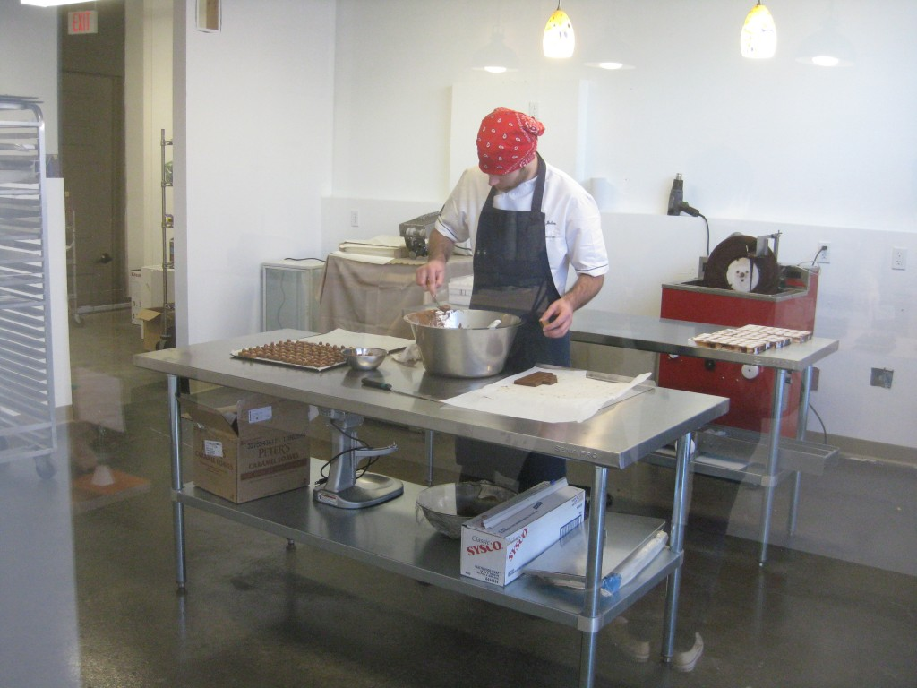 Julien making chocolates as viewed through the viewing room in the retail shop.