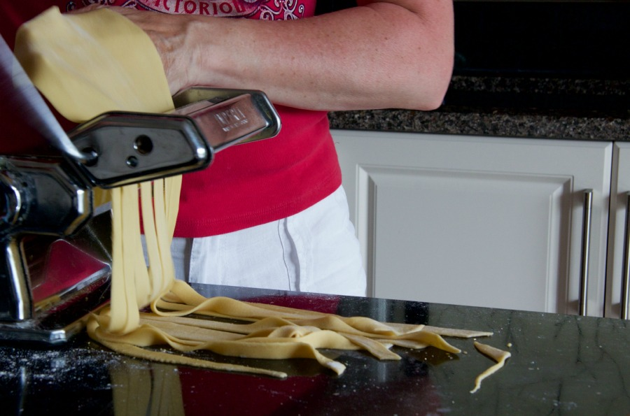 pasta sheet being cut into noodles